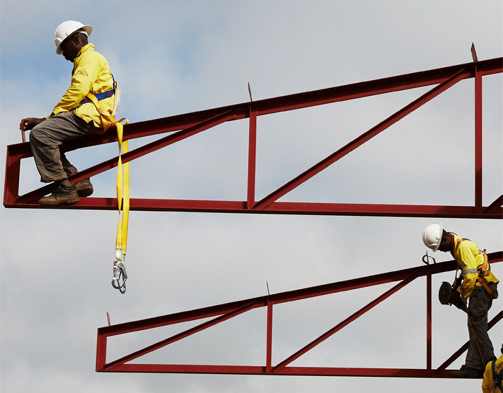 K2 Construction Zambia Workmen on steel beams of a steel framed building under construction